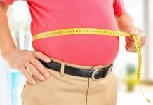 Otyłość brzuszna - mężczyzna mierzący sobie centymetrem obwód brzucha